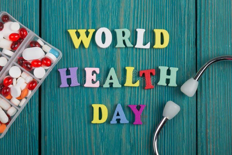文本& x22; 世界健康Day& x22;色的木信件、听诊器和药片 库存照片