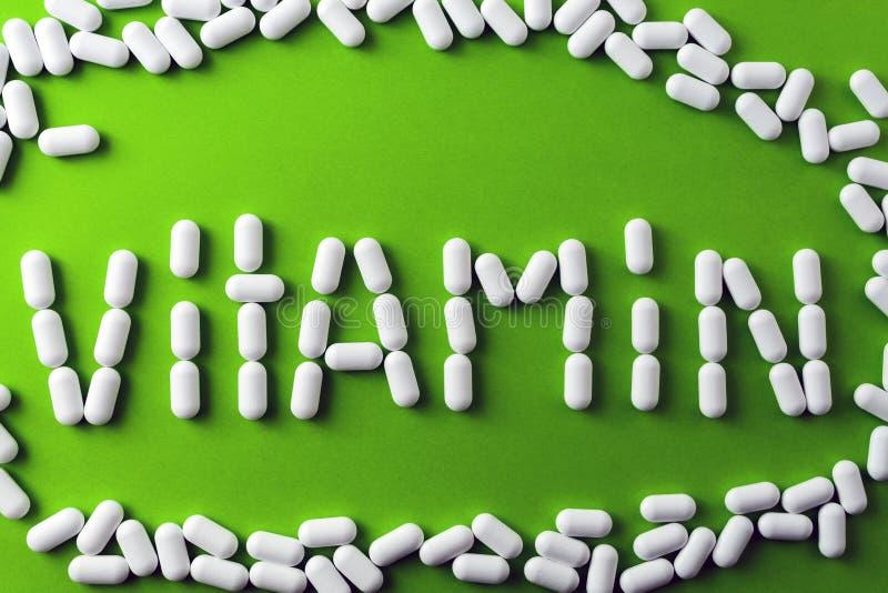 文本-维生素-白色药片,在绿色背景的片剂,在pilule附近 库存图片