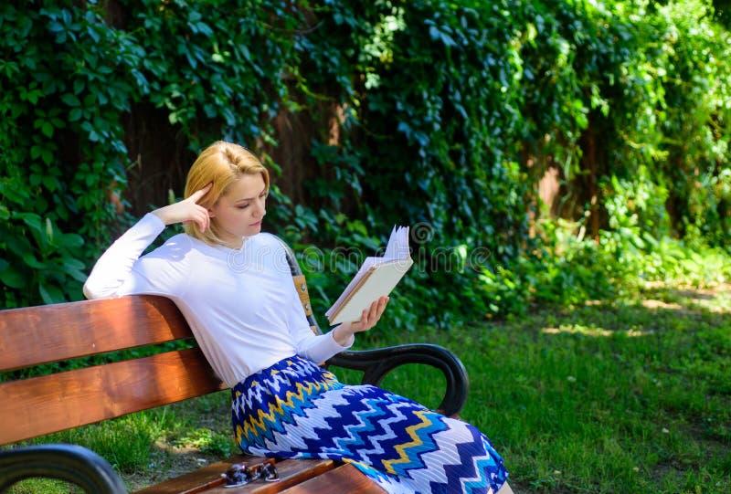 文艺的评论家 夫人俏丽的书痴繁忙的读的书户外晴天 妇女被集中的阅读书在庭院里 女孩 免版税库存图片