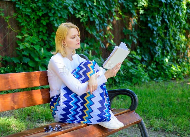 文艺的评论家 夫人俏丽的书痴繁忙的读的书户外晴天 妇女被集中的阅读书在庭院里 免版税库存照片