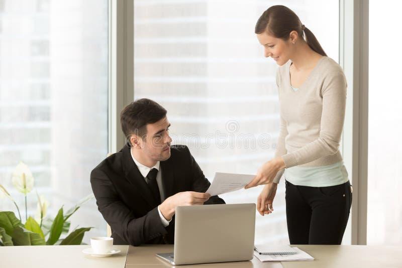 给文件的年轻人微笑的个人助手上司, paperw 免版税库存照片