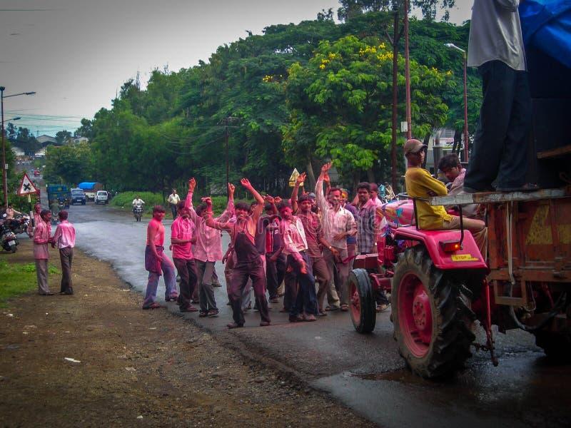 斋浦尔,拉贾斯坦印度,9月24日2007小组年轻人,在红色粉末盖的印度印度摆设酒宴者,跳舞在trac后 免版税库存图片