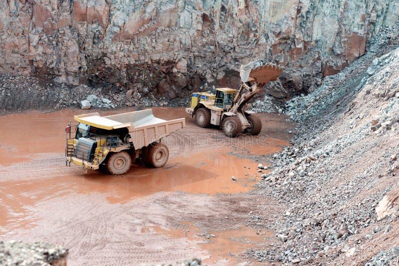 斑岩岩石猎物矿  装载倾销者卡车的推土机 库存图片