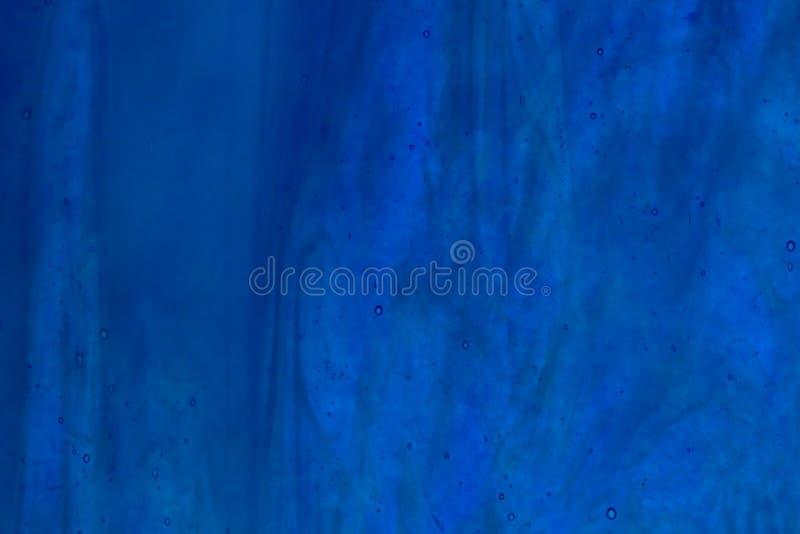 斑斑蓝色的玻璃被弄脏 免版税库存图片