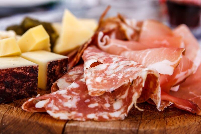 斑点板材和典型的意大利蒜味咸腊肠用乳酪和腌汁 图库摄影
