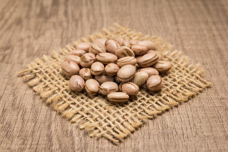 斑豆豆类 在黄麻方形的保险开关的五谷  木的表 免版税库存图片