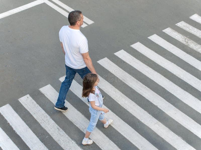 斑马线的侵入通过穿过的一个人和一个小孩子街道 在街道上的夏天 免版税库存照片