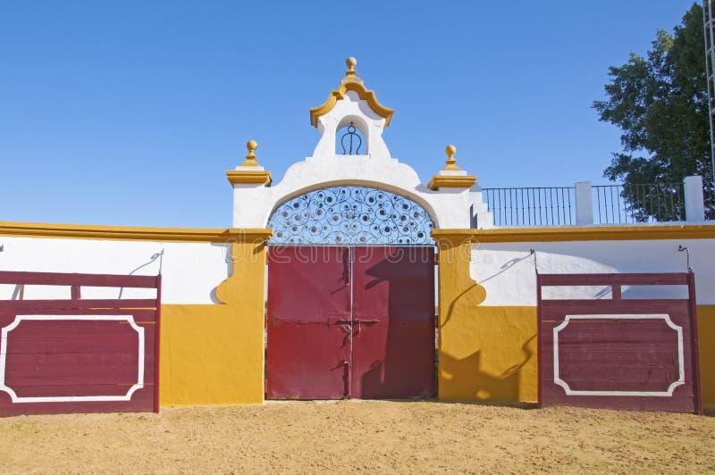 斗牛场的大红门,白墙,橙色装饰 西班牙伊斯拉市长 库存照片