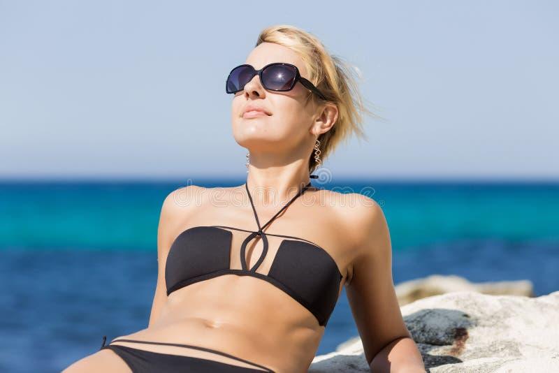 斜倚在岩石的比基尼泳装的妇女倾斜在她的手肘 免版税库存图片