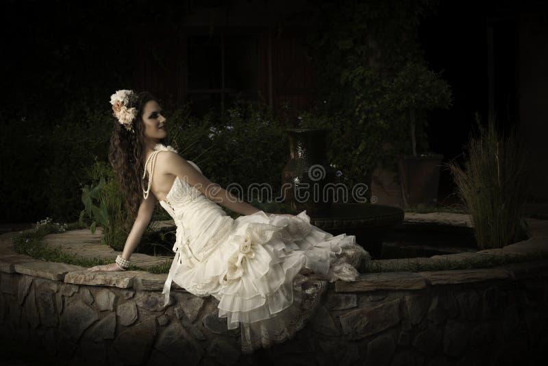 斜倚在庭院喷泉旁边的无背带的葡萄酒婚礼礼服的美丽的新娘 免版税库存图片