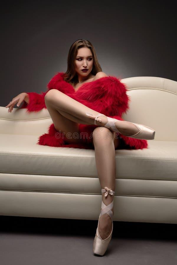 斜倚在沙发的红色皮大衣的华美的女孩 免版税库存图片