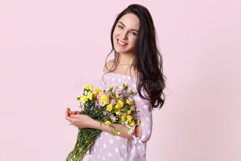 斜向一边射击喜悦的可爱的年轻女人拿着春天花,穿戴在圆点礼服,摆在桃红色背景,有 图库摄影