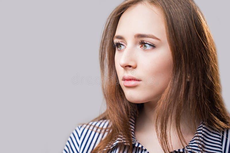 斜向一边美丽的年轻女人特写镜头画象  免版税库存图片
