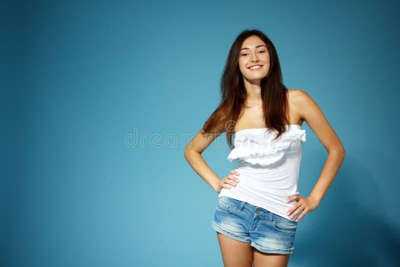 斜纹布短裤的美丽的青少年的女孩和在蓝色的白色上面 库存照片