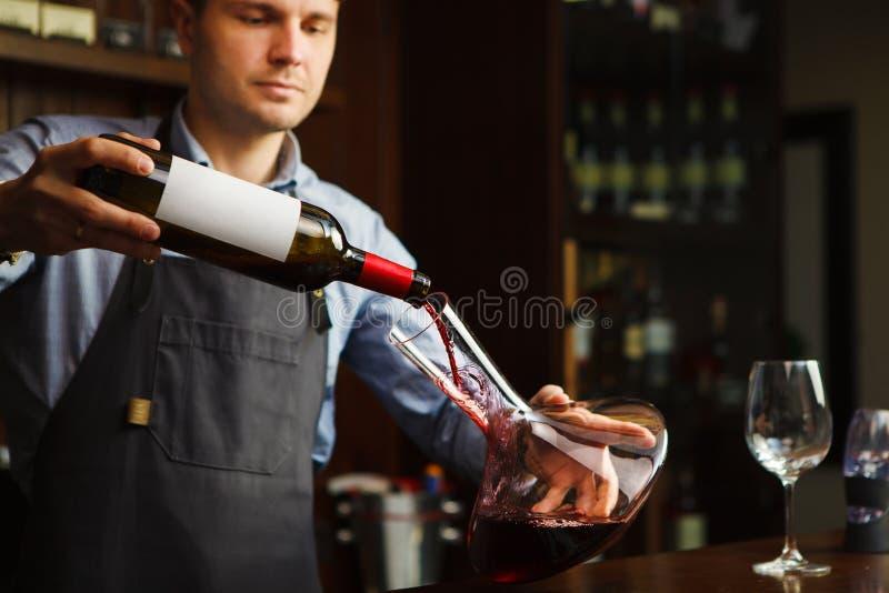 斟酒服务员倾吐的酒到从蒸馏瓶的玻璃里 男性等候人员 库存照片