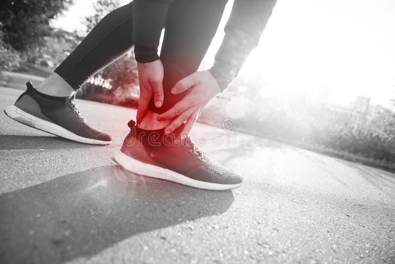 断扭转的脚腕-运行的体育运动伤害 运动人赛跑者感人的脚在痛苦中由于被扭伤的脚腕 免版税库存图片