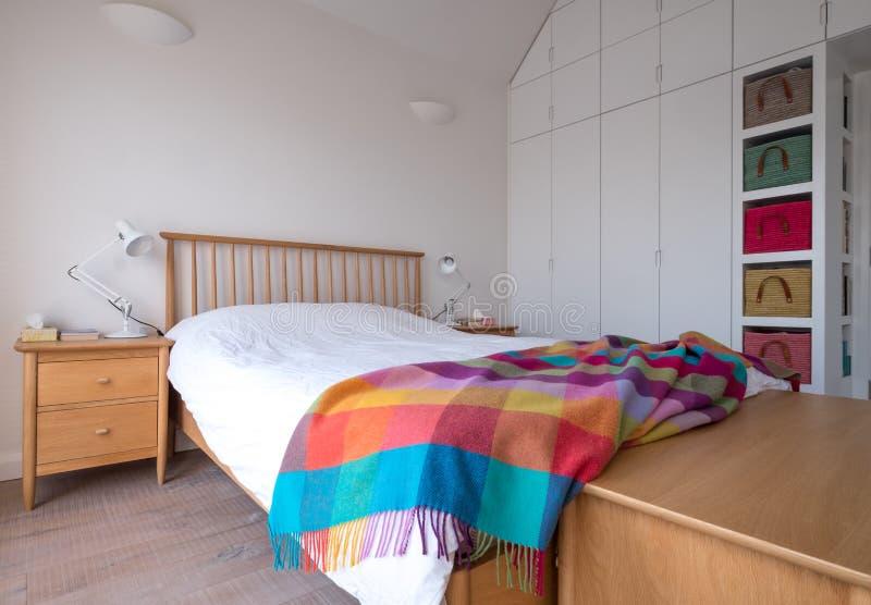 斯坎迪样式卧室内部与木卧室家具、白色被绘的墙壁、白色卧具和五颜六色的毯子 库存图片