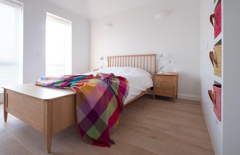 斯坎迪样式卧室内部与木卧室家具、白色被绘的墙壁、白色卧具和五颜六色的毯子 库存照片