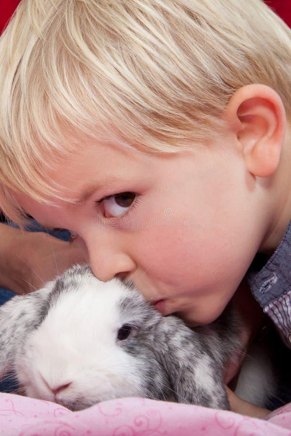斯堪的纳维亚年轻男孩的画象在演播室用兔子 免版税库存图片