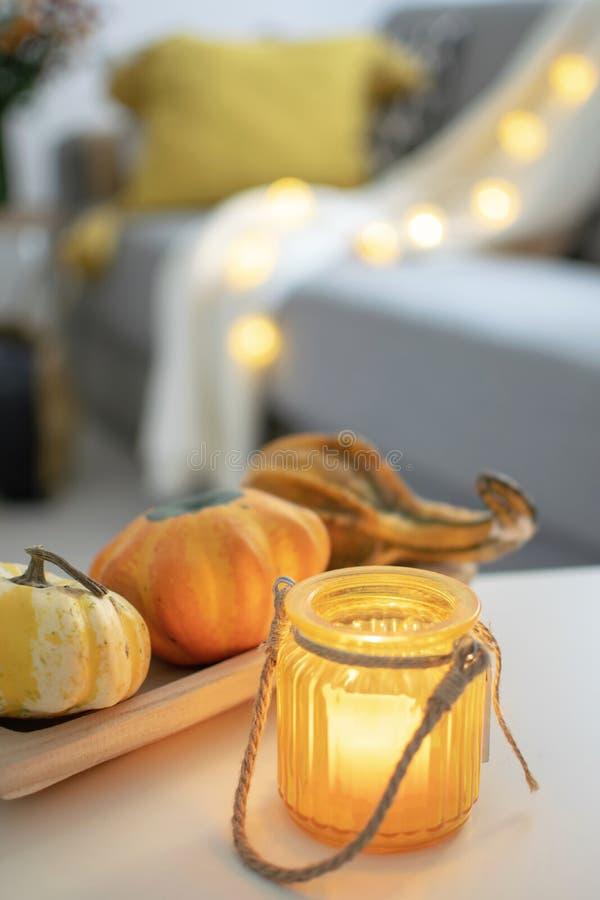 斯堪的纳维亚秋天在舒适客厅,沙发坐垫启发了家庭装饰-木盘子特写镜头用南瓜和蜡烛台 免版税库存照片