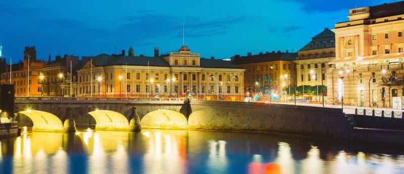 斯德哥尔摩瑞典 Norrbro,在Norrstrom水路的老石曲拱桥梁看法有光反射的在水中 图库摄影