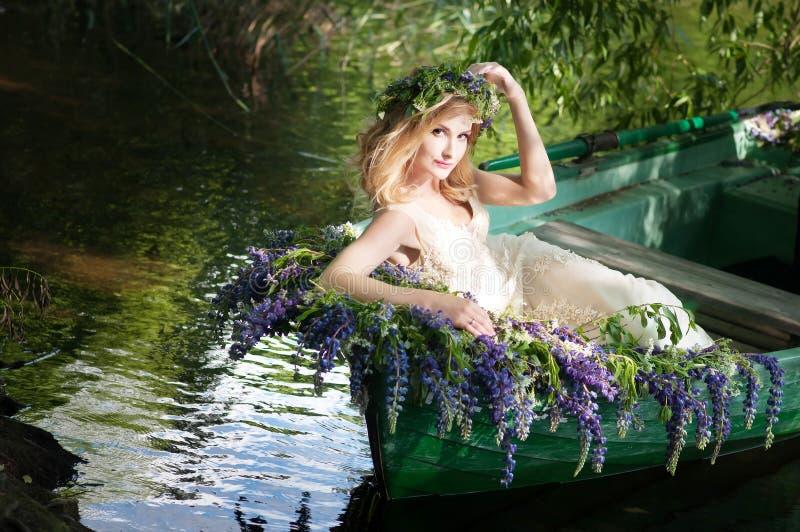 斯拉夫或波儿地克的妇女画象有坐在有花的小船的花圈的 夏天 图库摄影