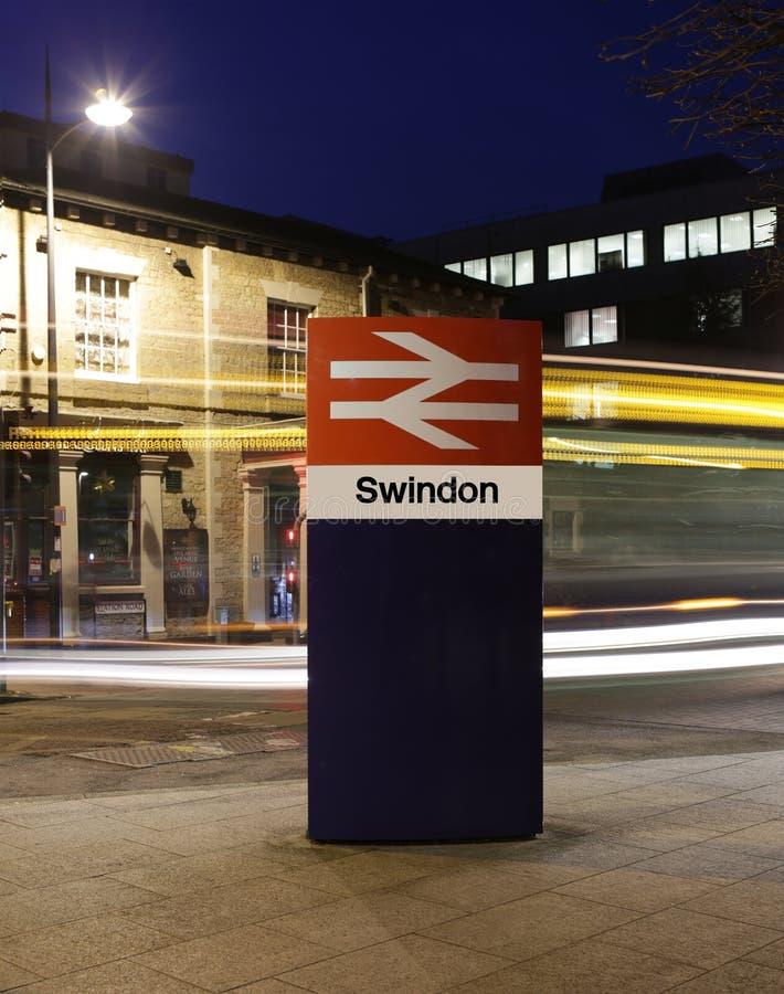 斯温登火车站在威尔特郡签字在与轻的足迹的晚上从一辆通过的公共汽车 免版税库存照片