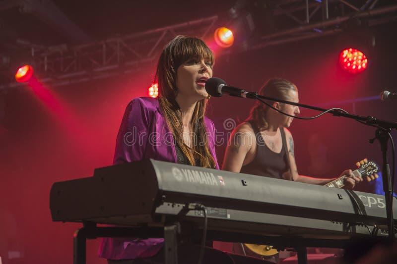贝斯牡鹿演奏键盘并且唱歌(在背景PJ Barth)中 图库摄影