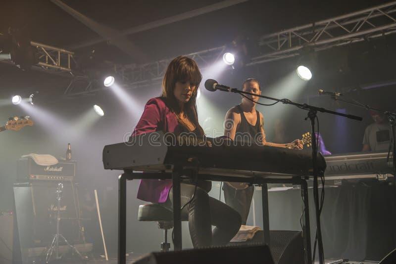 贝斯牡鹿演奏键盘并且唱歌(在背景PJ Barth)中 库存照片