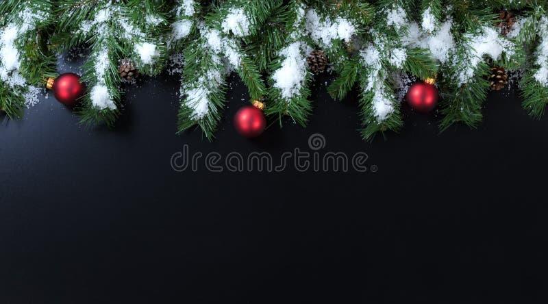 斯诺伊圣诞节分支与在黑背景的红色装饰品 免版税库存照片