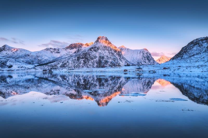 斯诺伊山和五颜六色的天空在水中反射了在日落 免版税库存照片