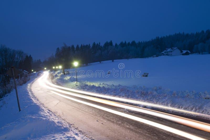 在夜冬天路的汽车足迹 免版税库存照片