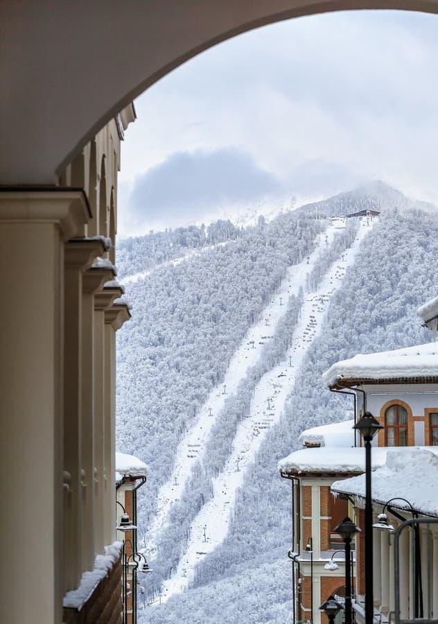 斯诺伊高尔基Gorod冬天山在多雪的滑雪倾斜和滑雪电缆车背景的滑雪胜地旅馆屋顶  美好的风景风景 库存图片