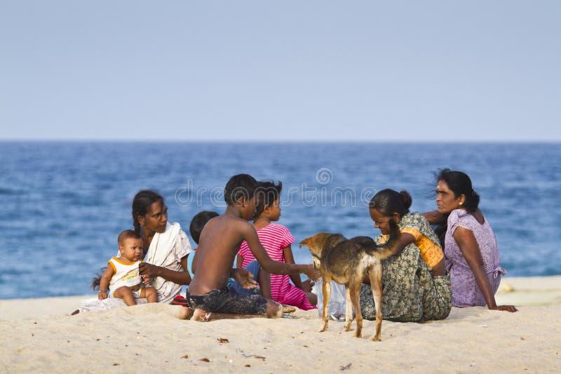 斯里兰卡家庭坐海滩,在拜蒂克洛,斯里兰卡 免版税库存图片