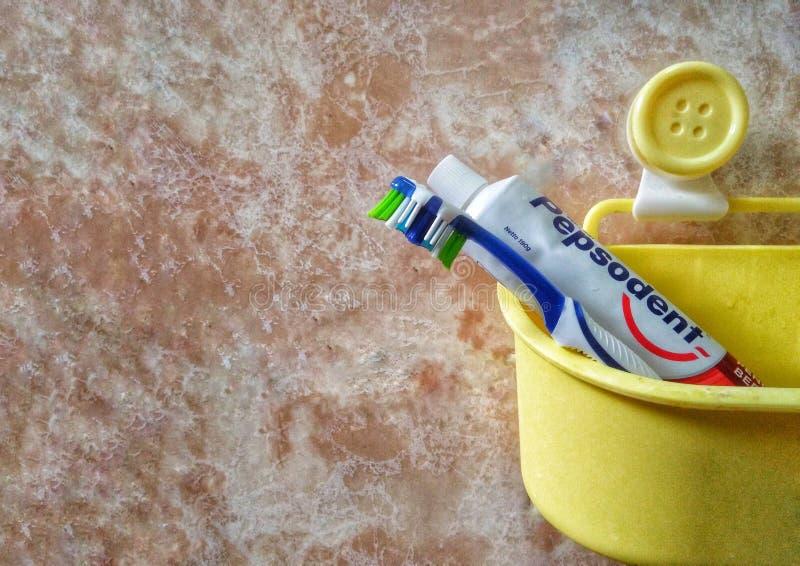 斯里巴加湾/文莱- 2019年5月19日:牙刷和Pepsodent牙膏的图象在一个黄色桶 库存图片