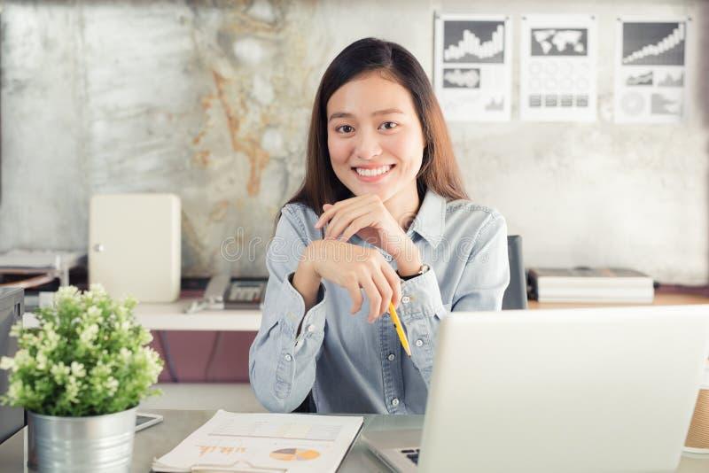 新一代亚洲人使用膝上型计算机的女商人在办公室 免版税库存图片