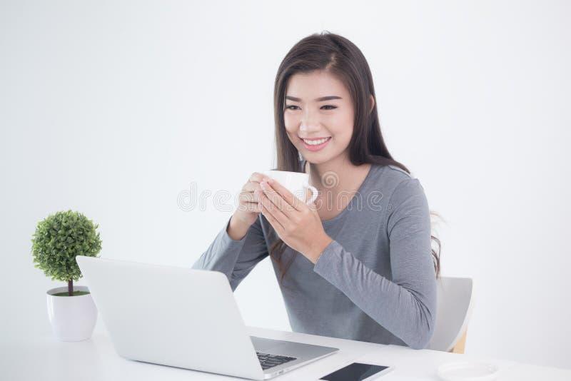 新一代亚洲人女商人坐的和饮用的咖啡 库存图片