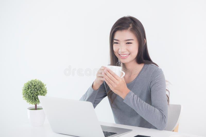 新一代亚洲人女商人坐的和饮用的咖啡 免版税库存照片