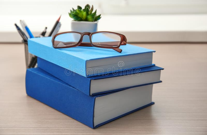新书和玻璃在桌上 免版税库存图片