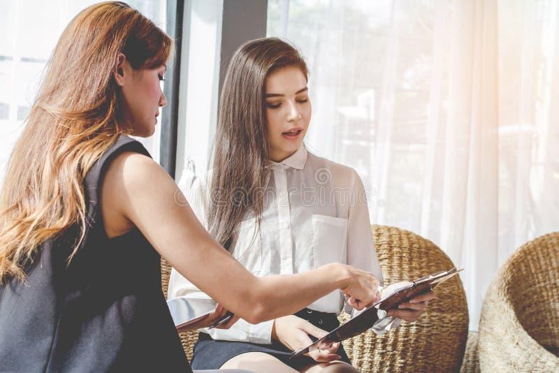 新亚洲人 妇女商人谈论的会合点,计划 经济化妆用品贸易  库存图片