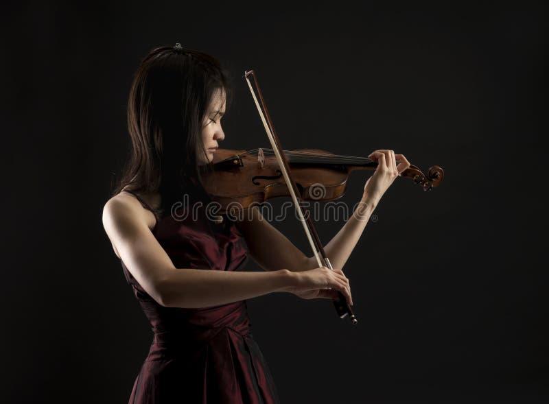 新亚洲妇女playng在黑色的小提琴 免版税库存照片