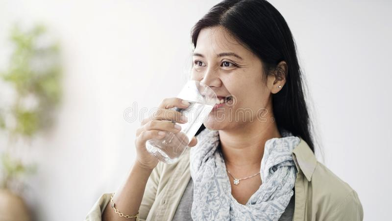 新亚裔妇女饮用水 库存图片