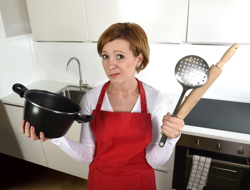 新人家厨师妇女在举行烹调的红色围裙在家厨房里平底锅和滚针哀伤在无能为力的重音被混淆和 免版税库存照片