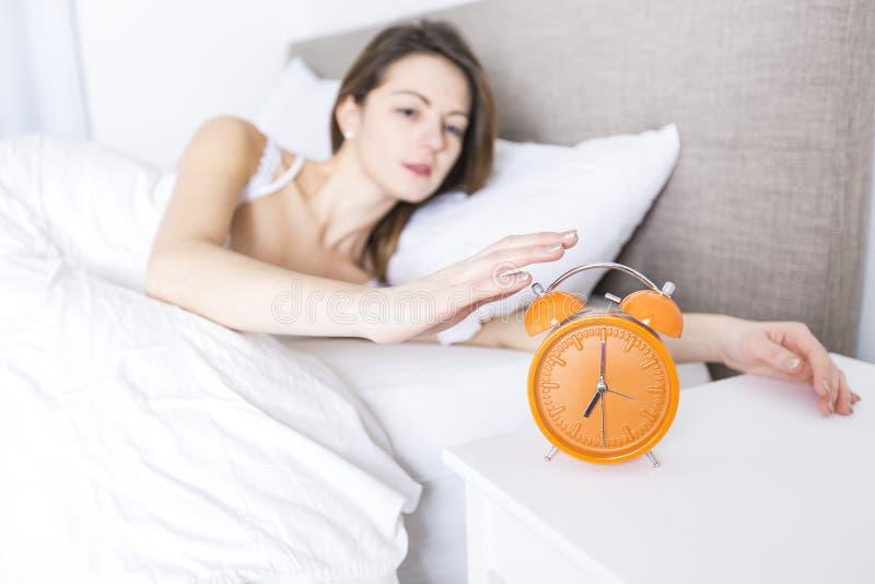 新休眠的妇女和闹钟在卧室在家 图库摄影