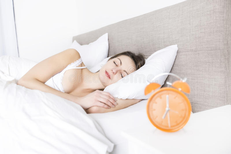新休眠的妇女和闹钟在卧室在家 免版税库存照片