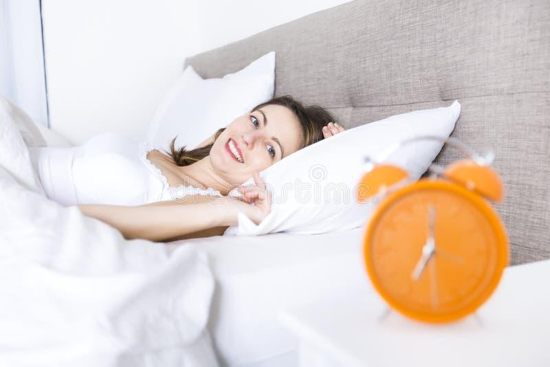 新休眠的妇女和闹钟在卧室在家 免版税图库摄影