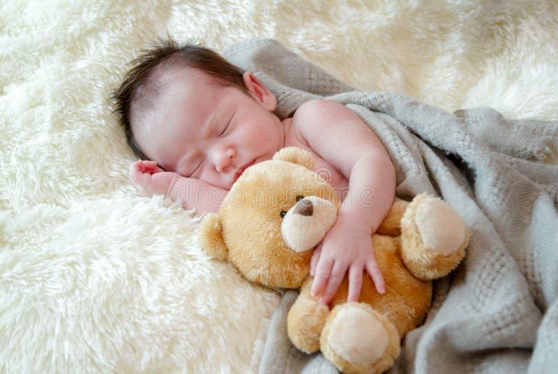 新出生的女婴与玩具玩具熊睡觉 库存图片