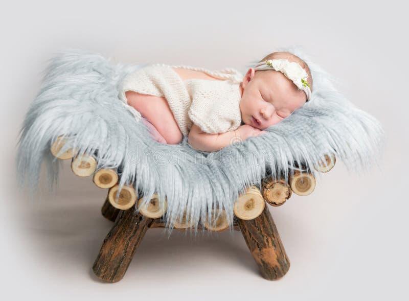 新出生的女婴在小木小儿床睡觉 免版税图库摄影