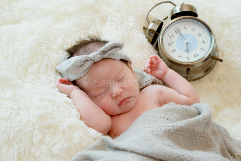 新出生的女婴赤裸在有时钟的毛皮毯子 免版税图库摄影