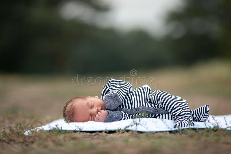 新出生的婴孩在草睡觉在公园 复制空间上面 免版税库存照片